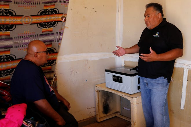 Big Navajo Energy President Dory Peters, right, provides information to Lorenzo Tahe about the solar-powered generator placed inside his home on Wednesday in Sanostee.
