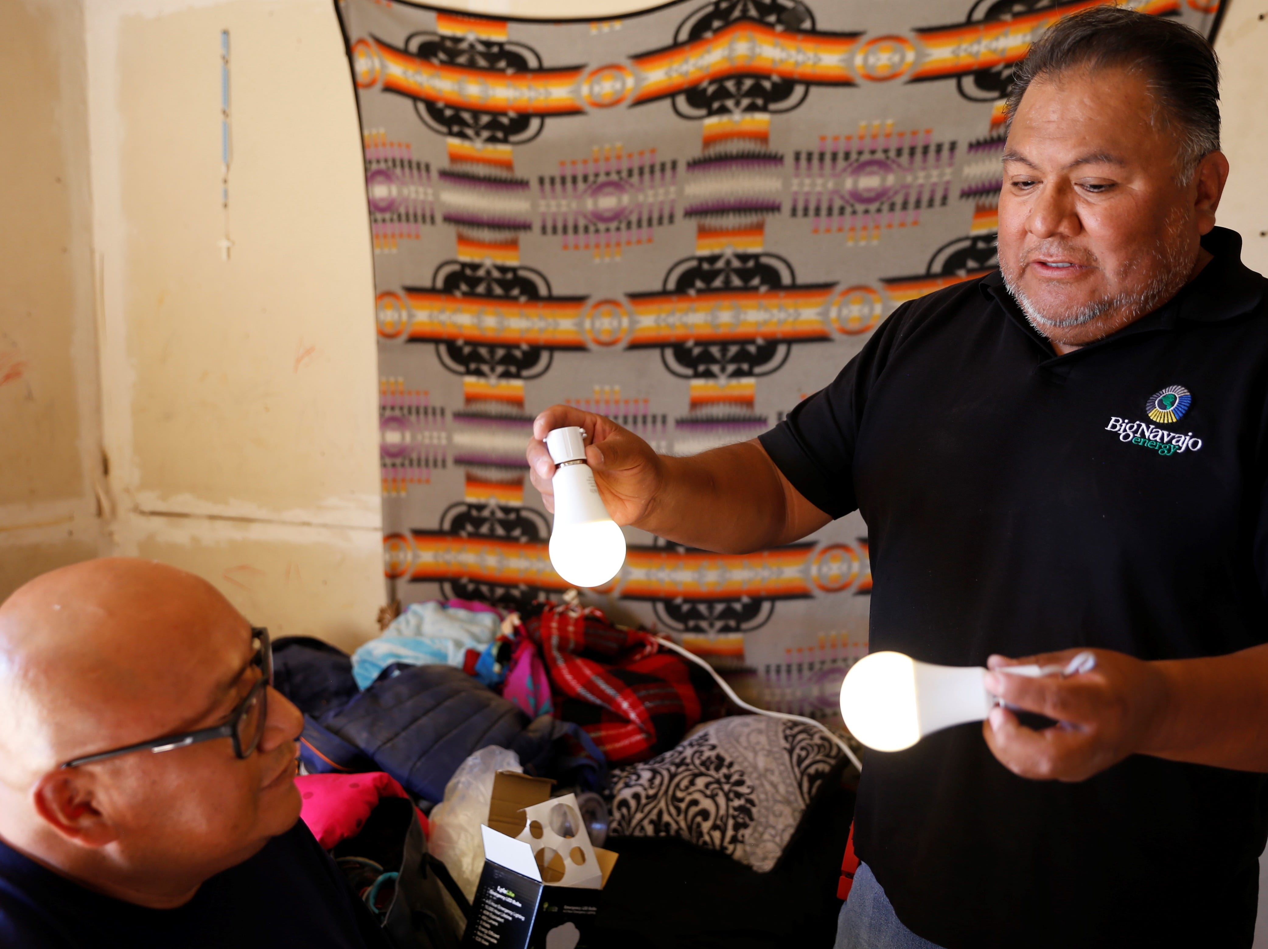 Lorenzo Tahe, left, listens as Big Navajo Energy President Dory Peters talks about rechargeable 5W bulbs on Wednesday in Sanostee.
