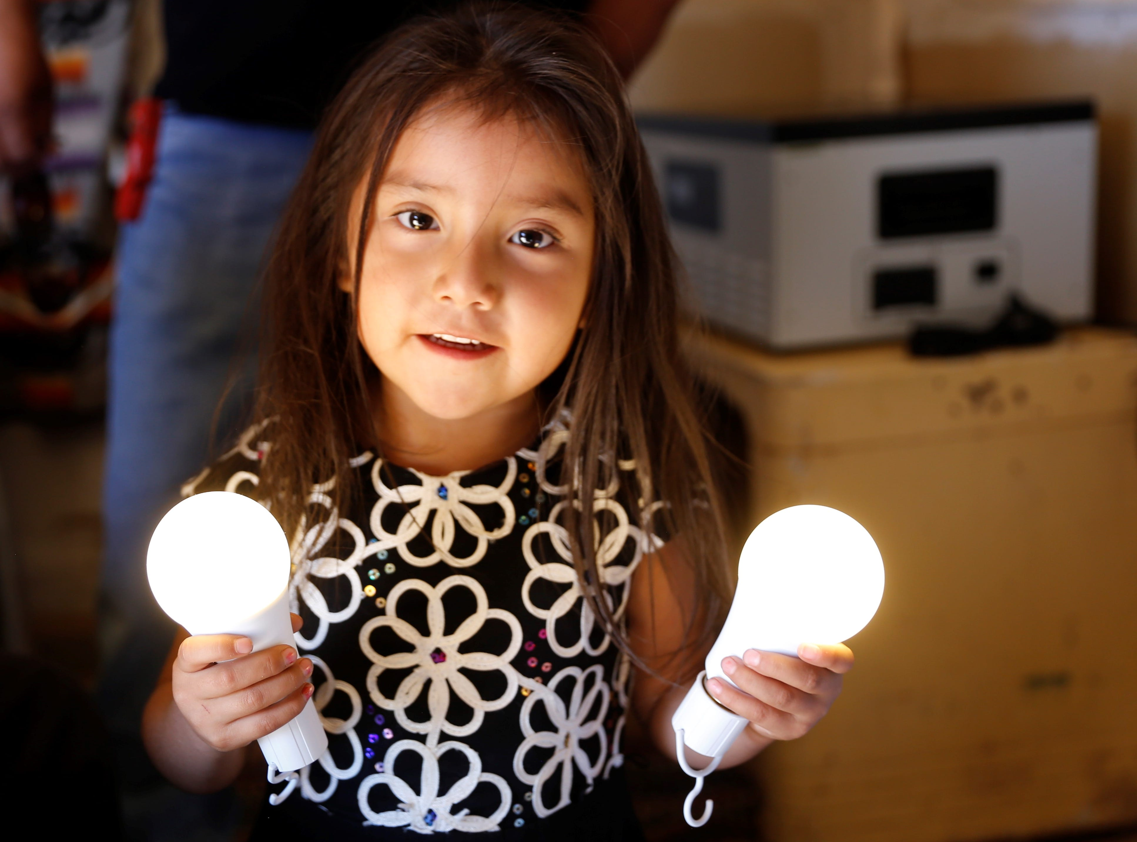 Lindsey Tahe was curious about the rechargeable bulbs donated by Big Navajo Energy on Wednesday in Sanostee.