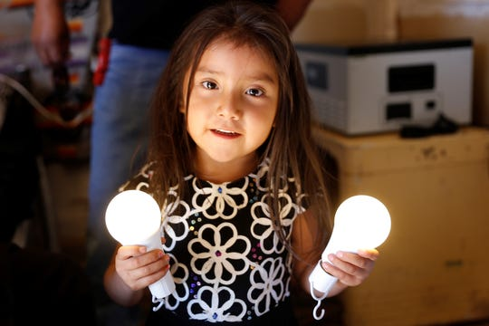Lindsey Tahe examines the rechargeable light bulbs donated by Big Navajo Energy for her family's new solar power electrical system on Wednesday in Sanostee.