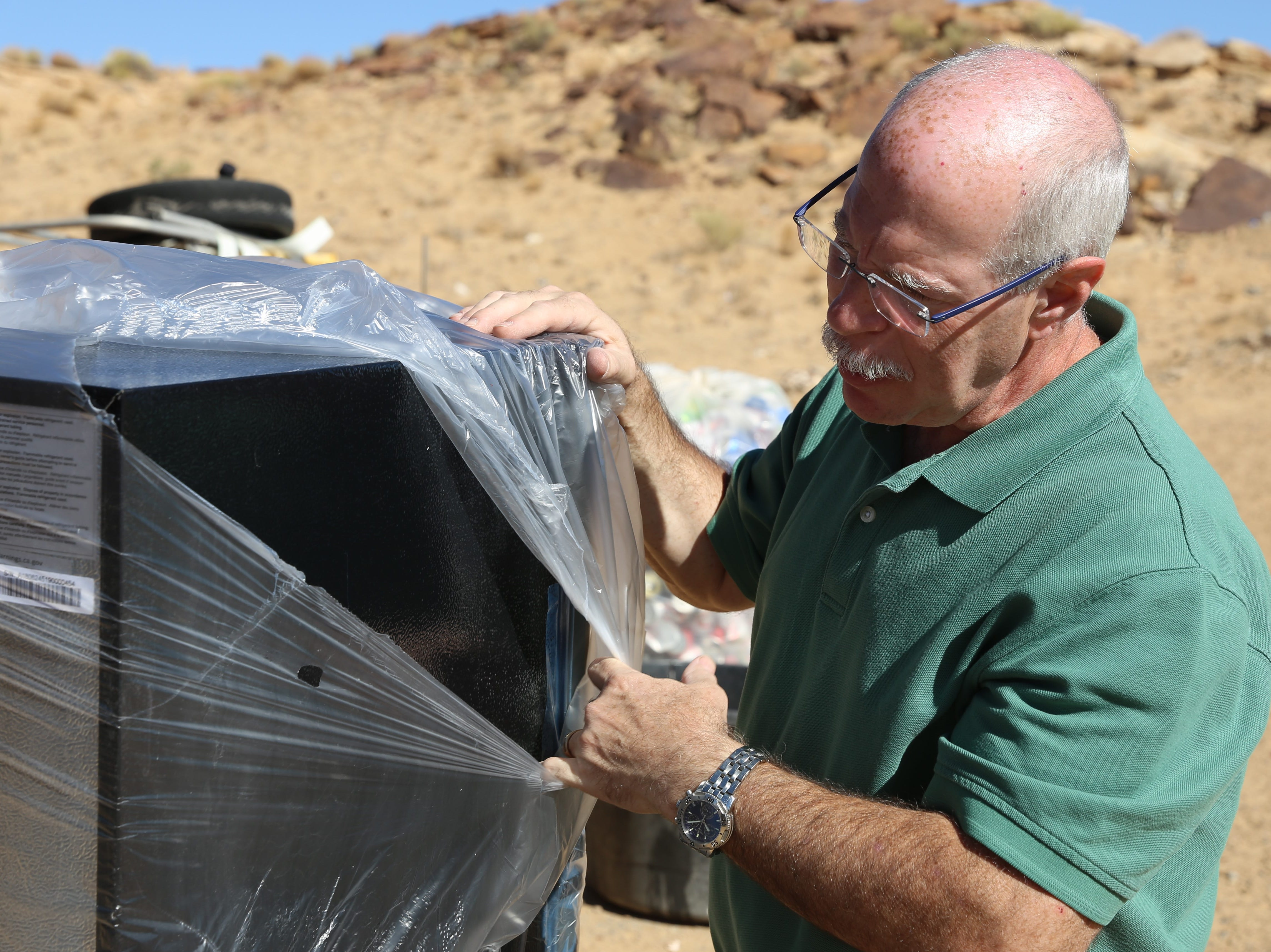 Cliff Samuels, project manager with Tacitus Ventures Corp., unwraps a refrigerator the company donated to the Tahe family on Wednesday in Sanostee.