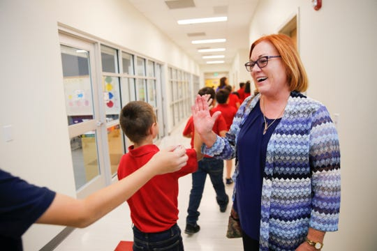 McCormick Elementary School Principal Lyn White high-fives her students as they head back to class Wednesday at their newly renovated school in Farmington.