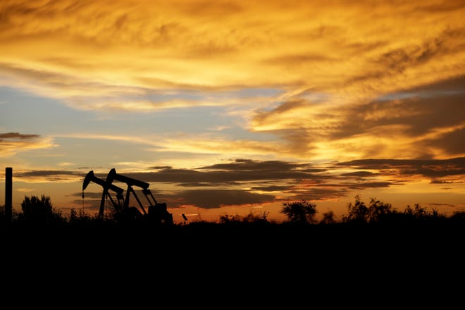 In this June 5, 2017, file photo pumpjacks work in an oil field at sunset after a thunderstorm passed through the area in Karnes City, Texas. The United States may have reclaimed the title of the world's biggest oil producer sooner than expected.