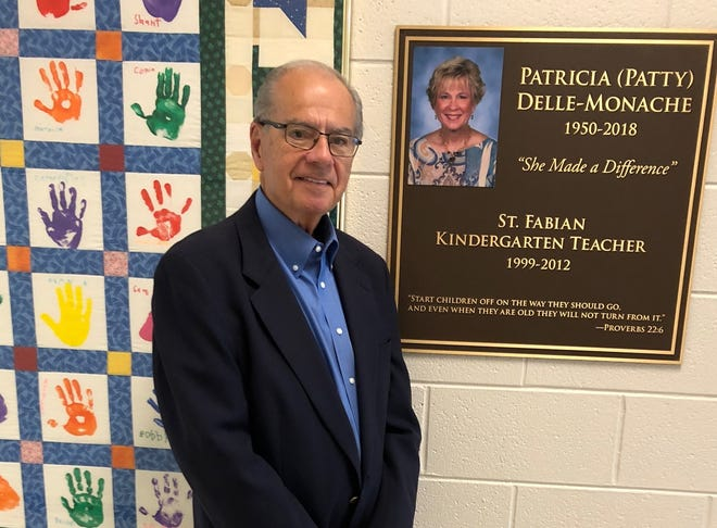John Delle-Monache at St. Fabian Catholic School with a new plaque that honors his late wife, Patricia, who taught kindergarten there for 13 years.