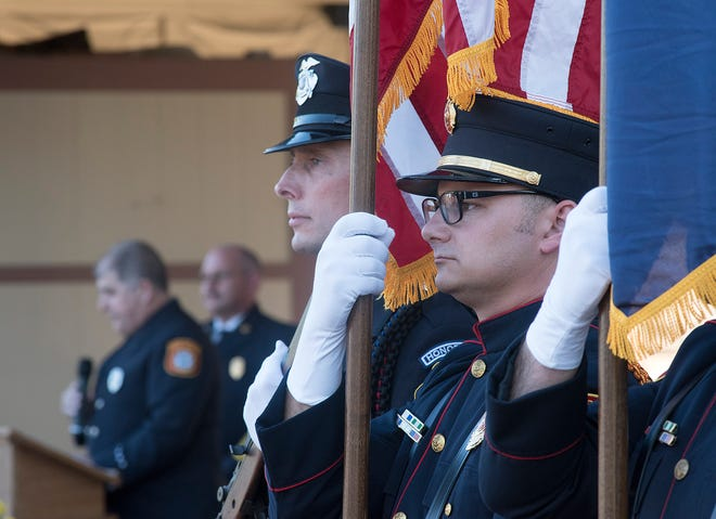 The honor guard stands as Farmington Hills firefighter Jim Etzin speaks.