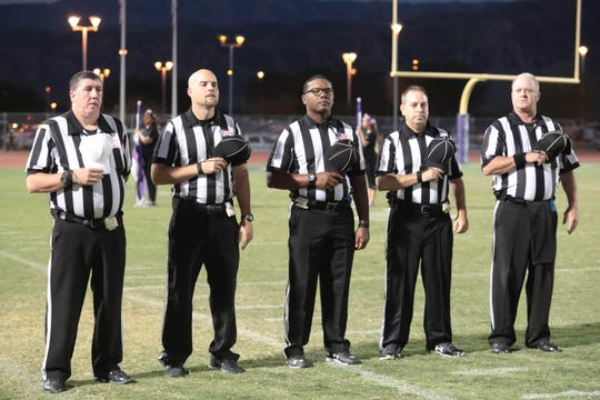 Referees stand for the national anthem during the Indio Sahdow Hills football game on Friday, September 7, 2018.