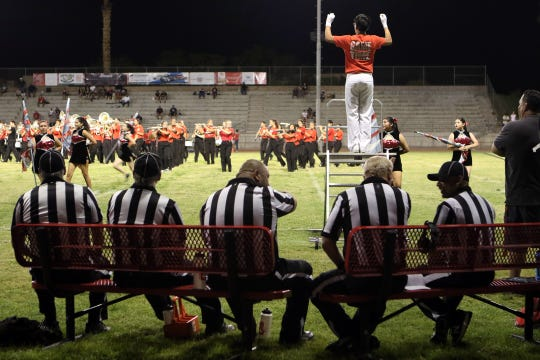 The referee crew takes a break on a hot night at Palm Springs High School during halftime of the Tustin-Palm Springs varsity football game.