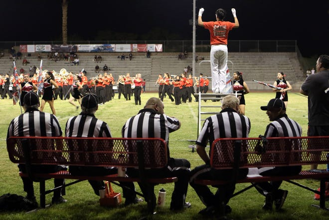 The referee crews takes a break on a hot night at Palm Springs High School during halftime of the Tustin-Palm Springs varsity football game.