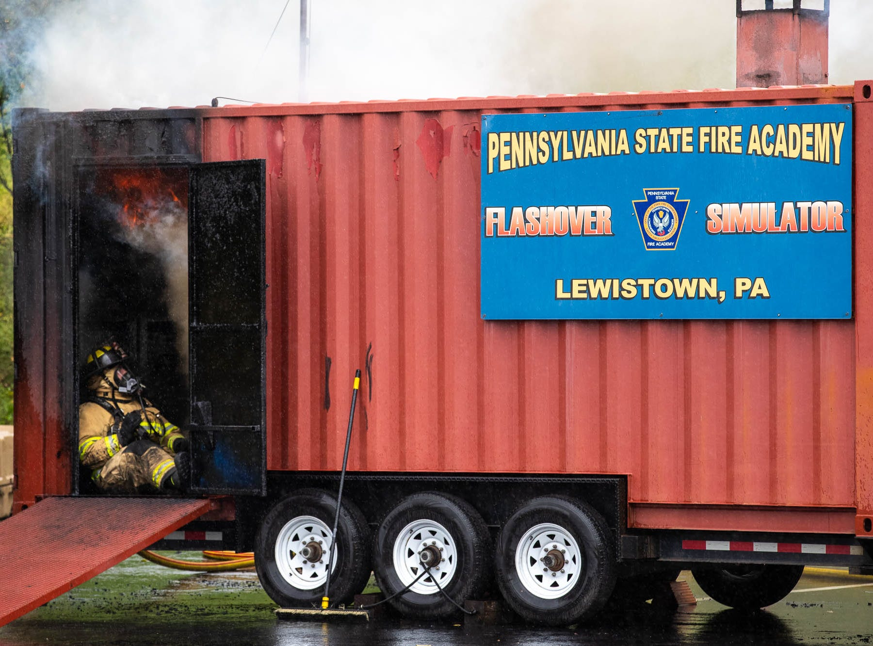 Flames shoot overtop of firefighters as they take part in a flashover simulator at the Hanover Area Fire & Rescue Clover Lane station, Saturday, Sept. 8, 2018, in Penn Township.