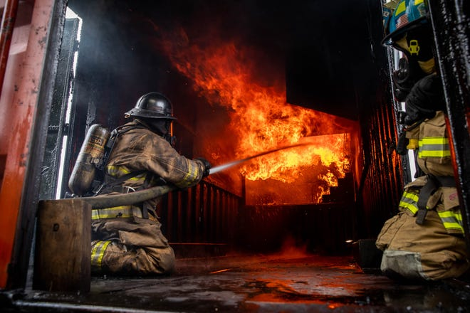 An instructor douses flames following a run of a flashover simulator at the Hanover Area Fire & Rescue Clover Lane station, Sunday, Sept. 9, 2018, in Penn Township.
