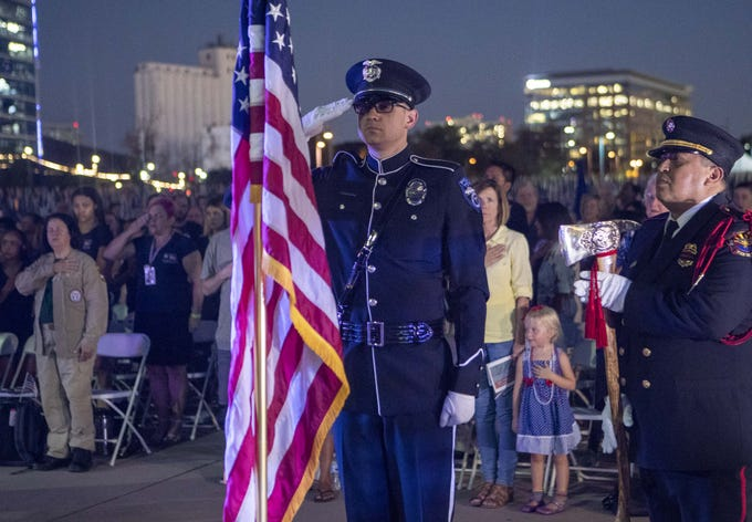 Tempe police Detective Matt DeCourval and Lorenzo Vizcarra, of the Tempe Fire Medical Rescue Department, salute the U.S. flag during the ceremony at the Healing Field at Tempe Beach Park on Sept. 11, 2018. This is an annual memorial to commemorate the Sept. 11, 2001, terrorist attacks on U.S. soil.