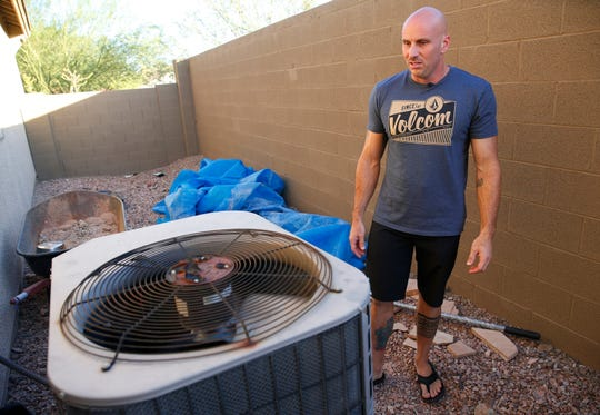 Mike Montgomery looks at his air-conditioning unit at his home in Anthem on Sept. 10, 2018. He purchased his house last year and it came with a home warranty. When the air conditioner went out, he couldn't get it repaired in a timely manner.