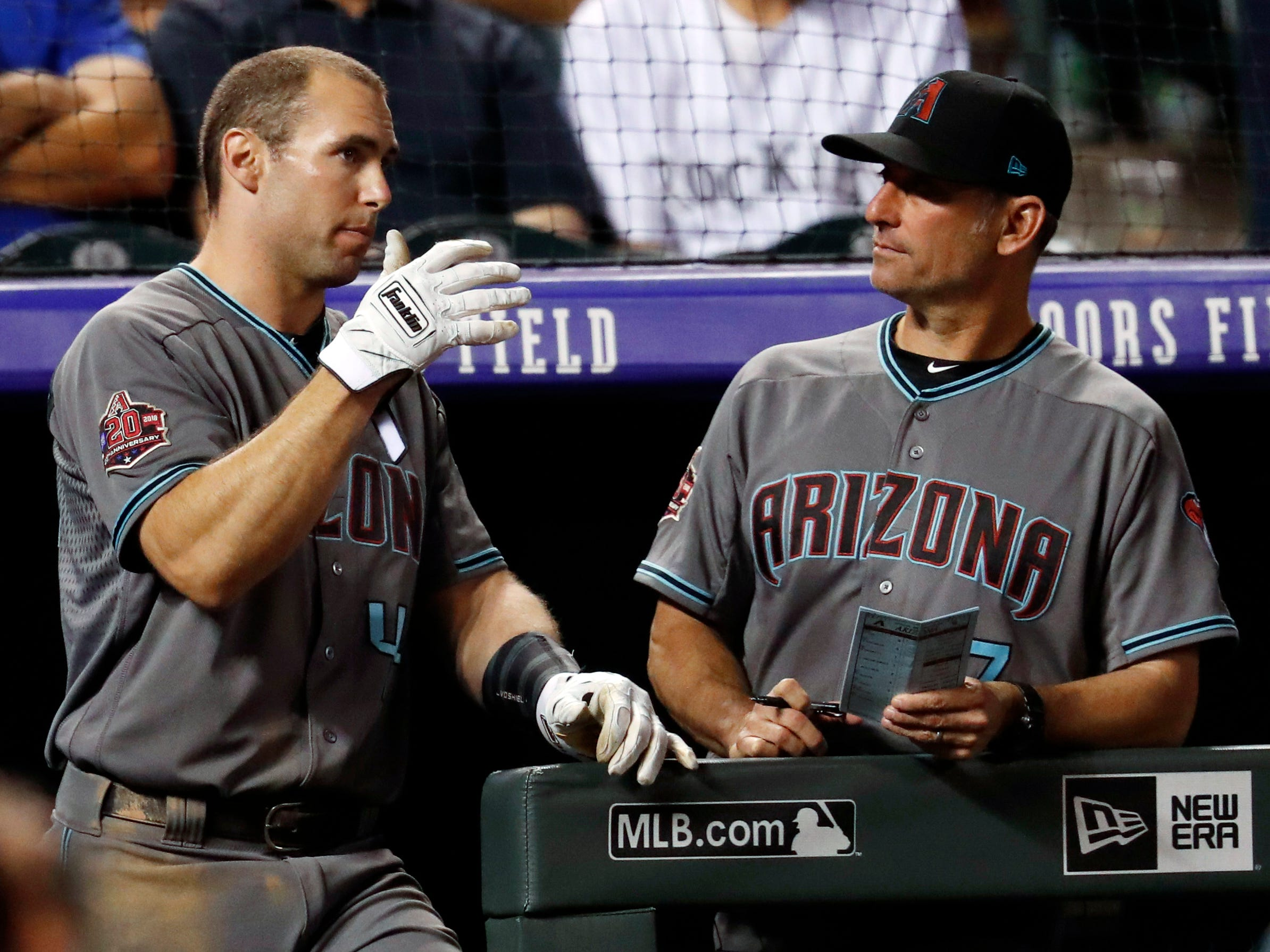 Arizona Diamondbacks first baseman Paul Goldschmidt, left, talks with manager Torey Lovullo as the Diamondbacks bat against the Colorado Rockies in the ninth inning of a baseball game, Tuesday, Sept. 11, 2018, in Denver. Arizona won 6-3.