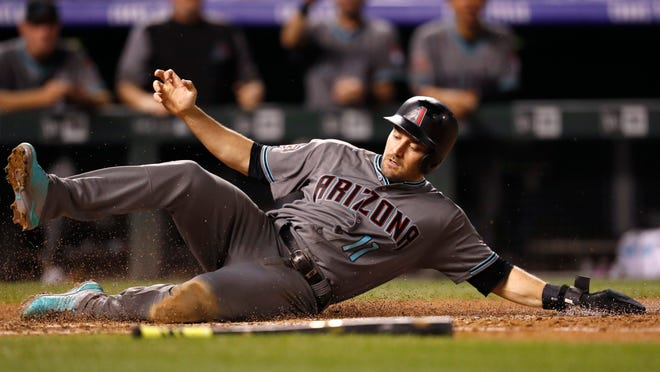 Arizona Diamondbacks' A.J. Pollock slides safely across home plate to score on a triple hit by Ketel Marte off Colorado Rockies starting pitcher Antonio Senzatela in the sixth inning of a baseball game, Tuesday, Sept. 11, 2018, in Denver.