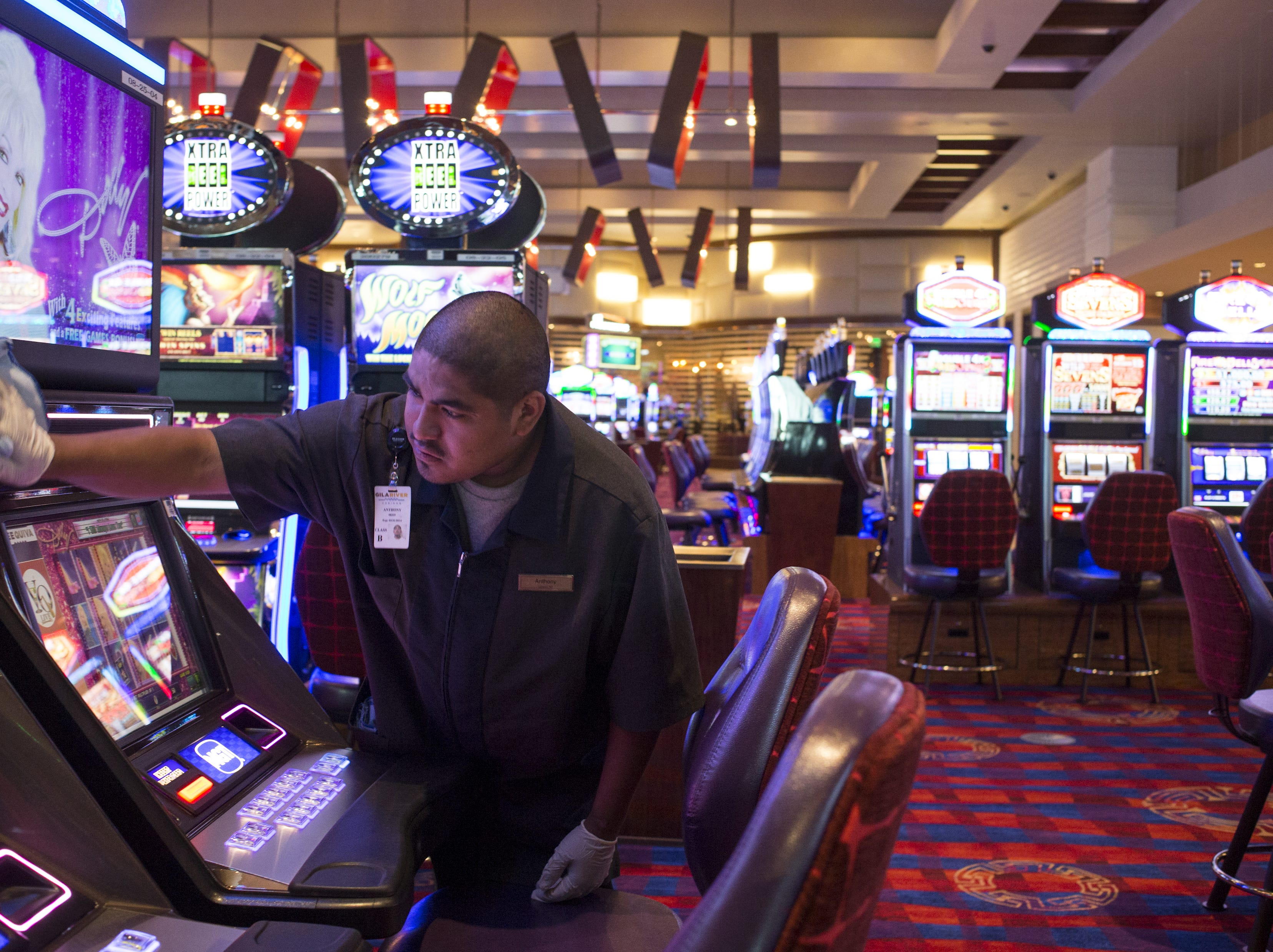 Anthony Jackson cleans a slot machine in the casino at Vee Quiva Hotel & Casino in Laveen.