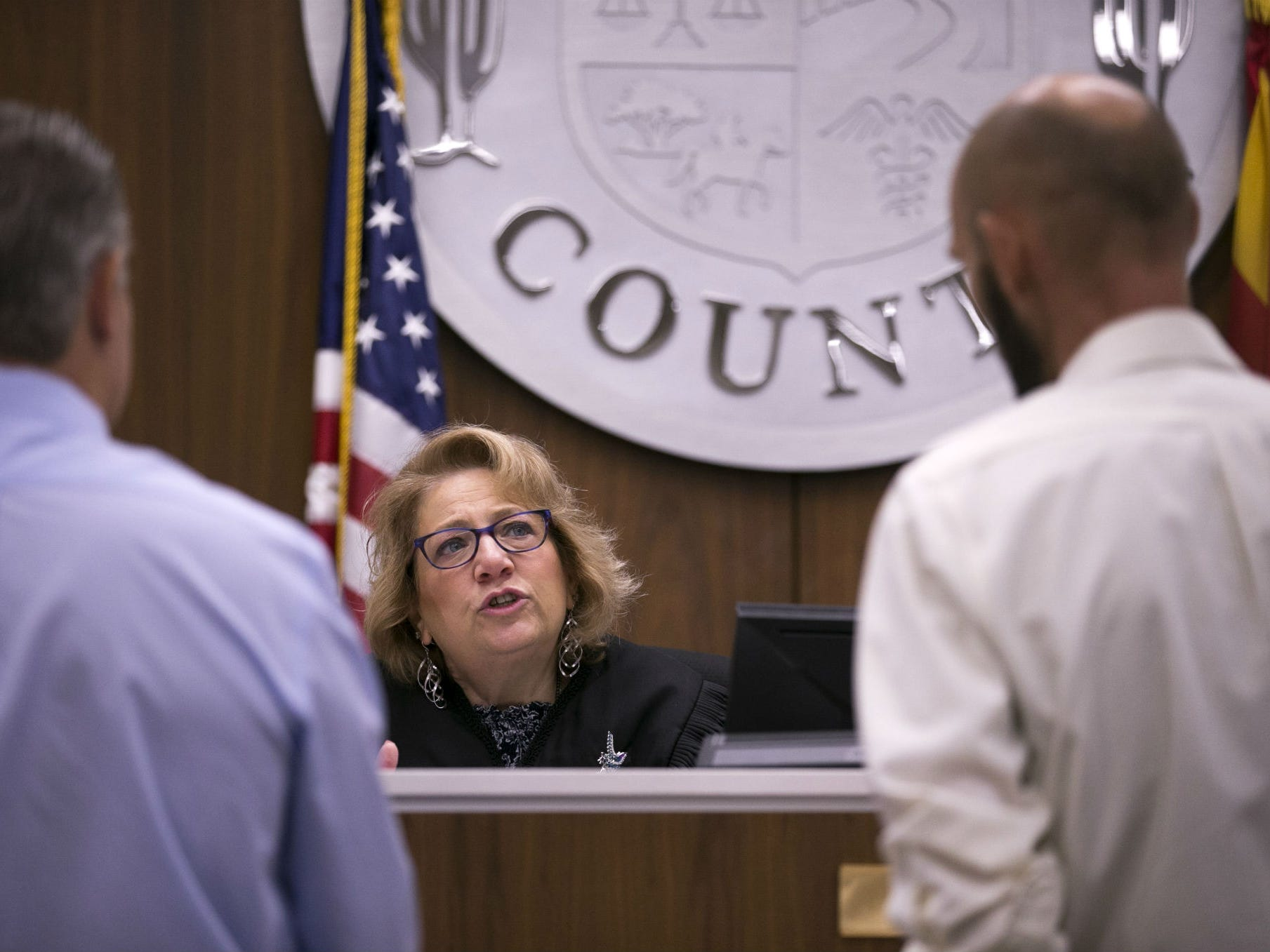 "Judge Anna Huberman speaks with a tenant (right) as Scott Clark, an attorney for the landlord, looks on during an eviction hearing at the Country Meadows Justice Court in Tolleson on Aug. 15, 2018. ""I think the problems are structural,"" Huberman says of the county's evictions process."