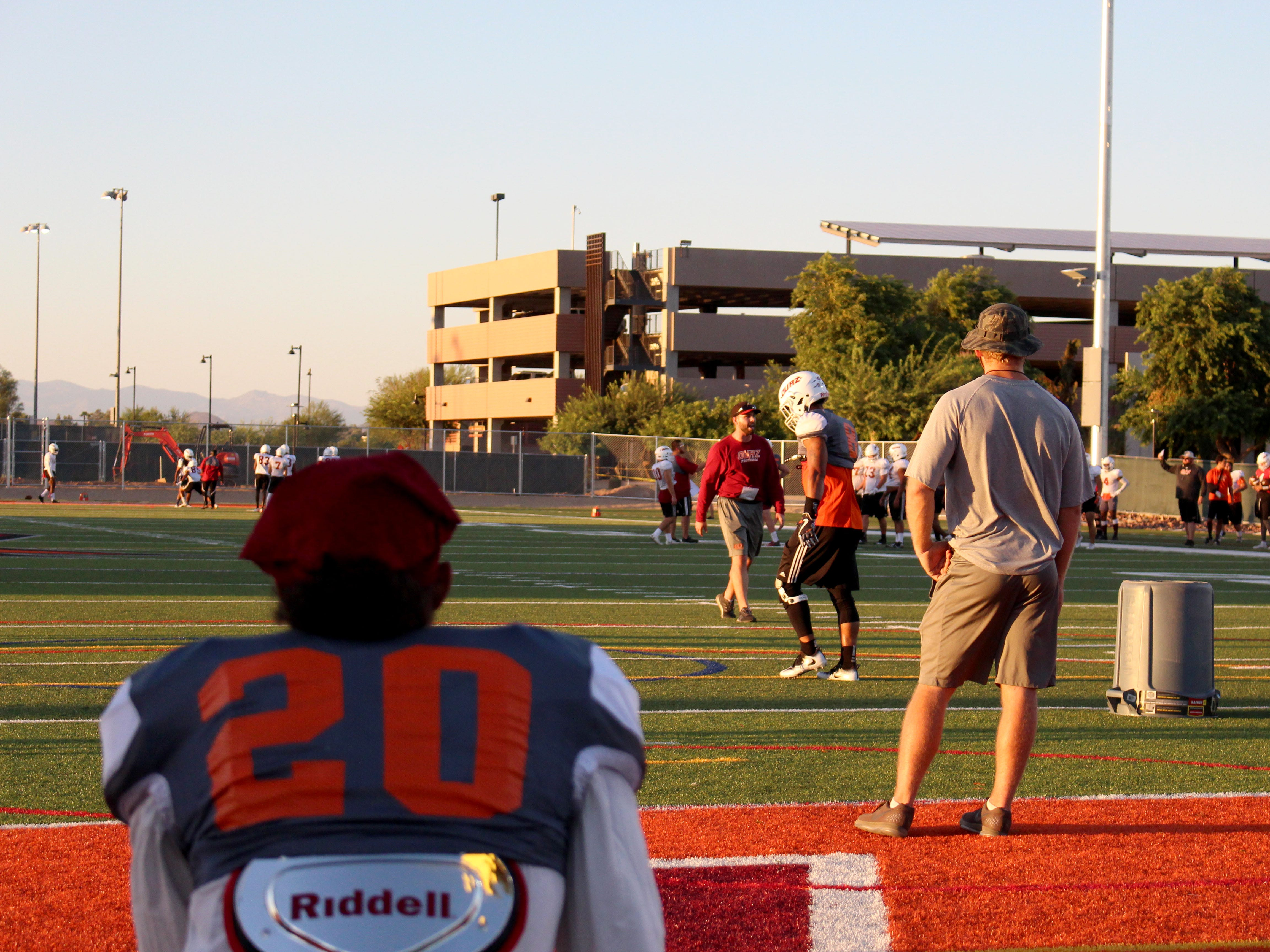 OUAZ's Joshua Vizcaya watches the team practice as he takes a knee in the end zone on Tuesday night in Surprise on Sept. 11, 2018.