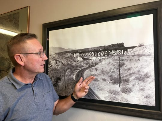 Mike Levin shows off a picture of an old-time train crossing Tucson's desert.