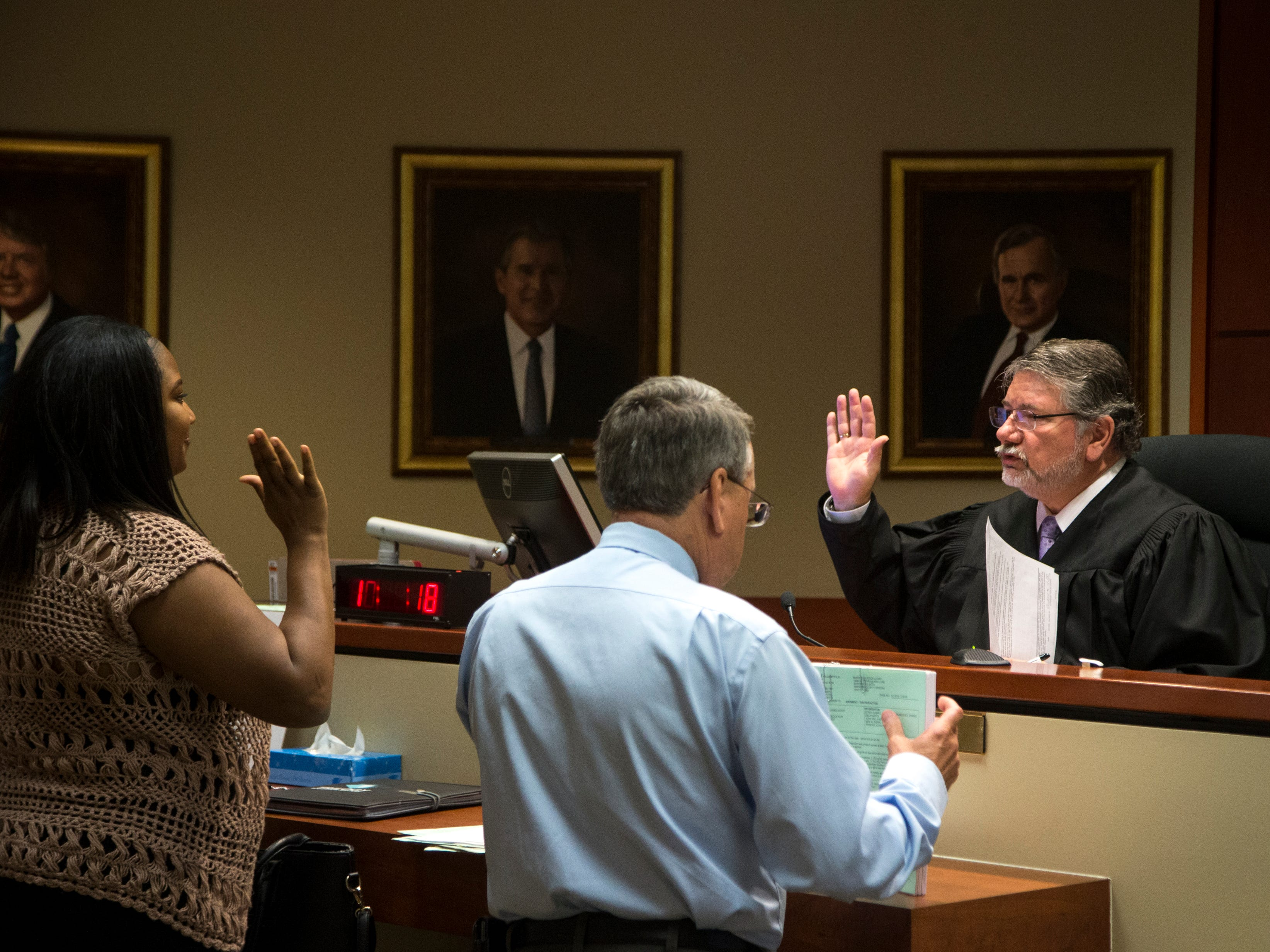 Judge Donald Watts swears in Dakiesha Owens during her eviction hearing on April 24, 2018, in Manistee Justice Court in Surprise. Maricopa County's landlords filed 62,800 eviction lawsuits last year, and more than two-thirds of those resulted in eviction judgments.
