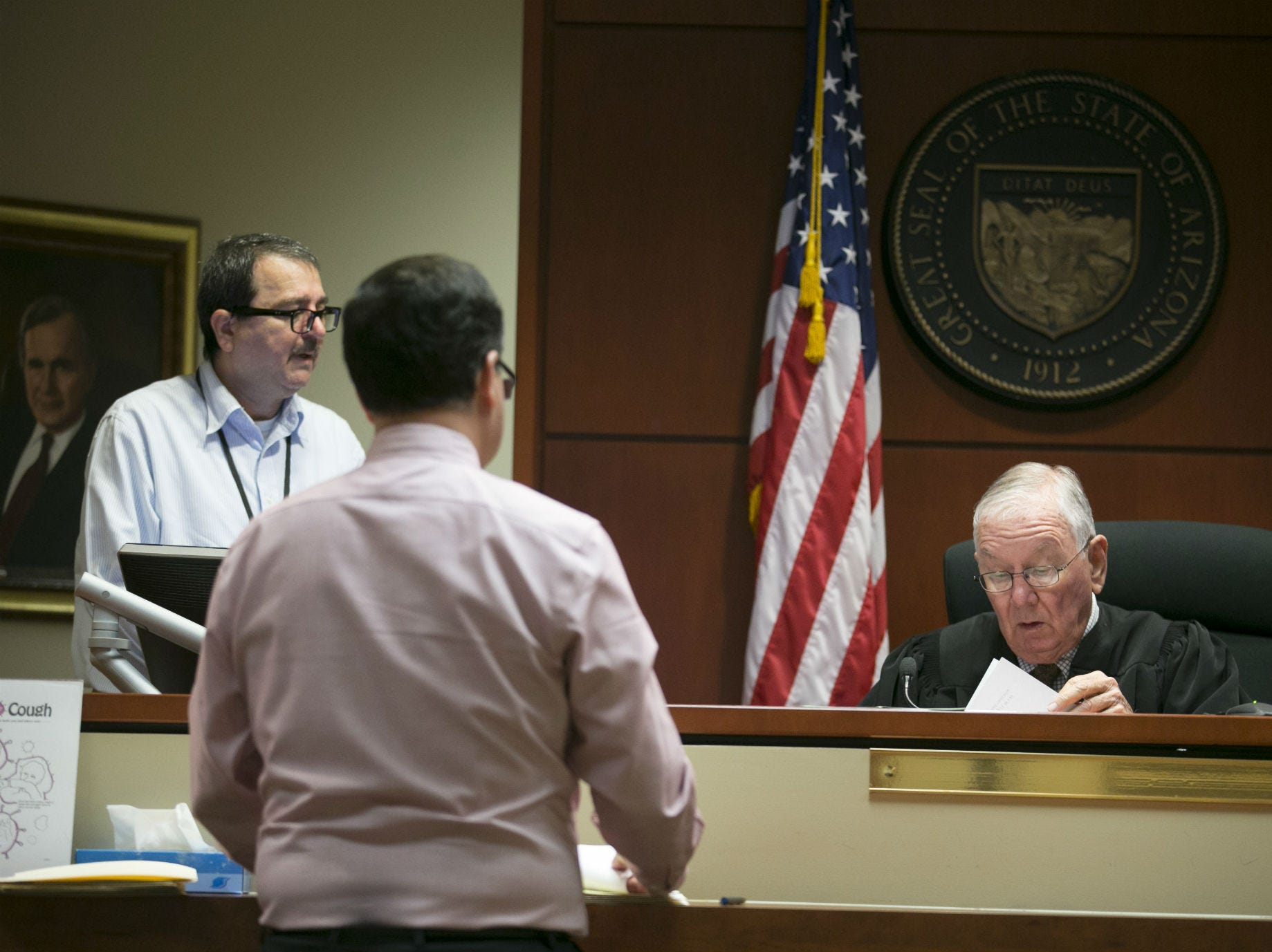Judge Pro Tempore Reid Southern checks out paperwork as Paul Henderson (center left), an attorney for the landlord, and court clerk Carlos Arce look on during an eviction court hearing at the Justice Court in Surprise on Aug. 16, 2018. Before a tenant's eviction hearing, the landlord's attorney usually offers a stipulated judgment that often produces the same result as if a tenant hadn't shown up at all. People admit they didn't pay rent. They agree to pay a monetary judgment that can be hundreds of dollars more than the rent they owed. And still they have to move out.