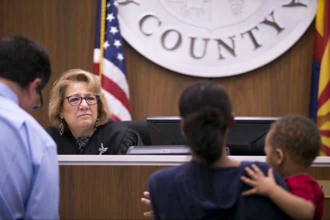 Judge Anna Huberman speaks with a tenant holding her child as Paul Henderson, an attorney for the landlord, looks on during an eviction hearing at the Country Meadows Justice Court in Tolleson on Aug. 15, 2018. Most landlords build grace periods into their leases, allowing tenants an extra few days to pay. But once that deadline passes, the eviction cycle kicks into gear.