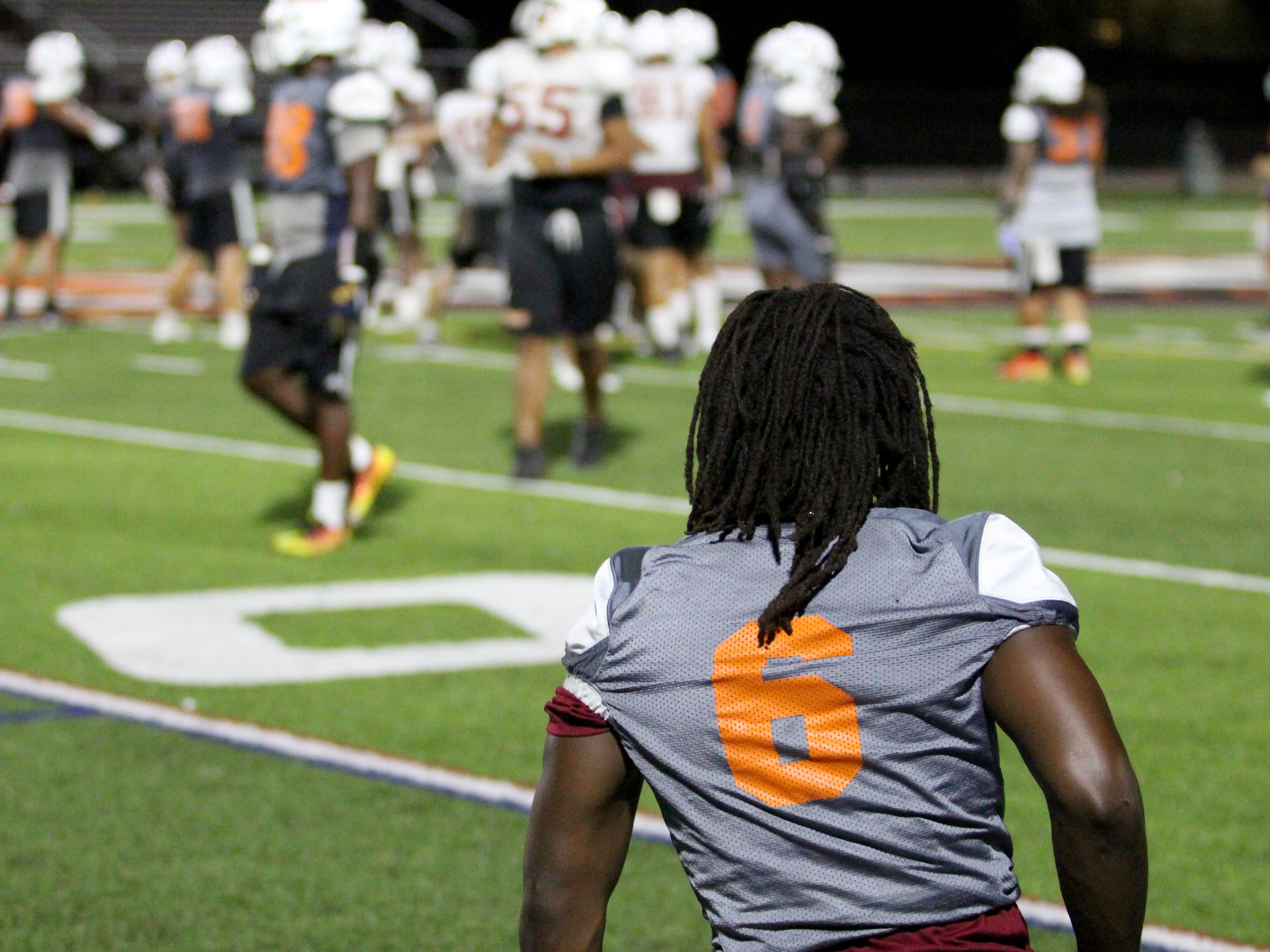 OUAZ's Amare Burks takes a knee and watches practice on Tuesday night in Surprise on Sept. 11, 2018.