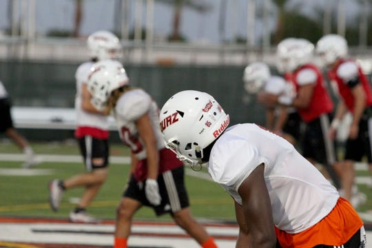 OUAZ players get set on the line of scrimmage before the snap at practice on Tuesday night in Surprise on Sept. 11, 2018.