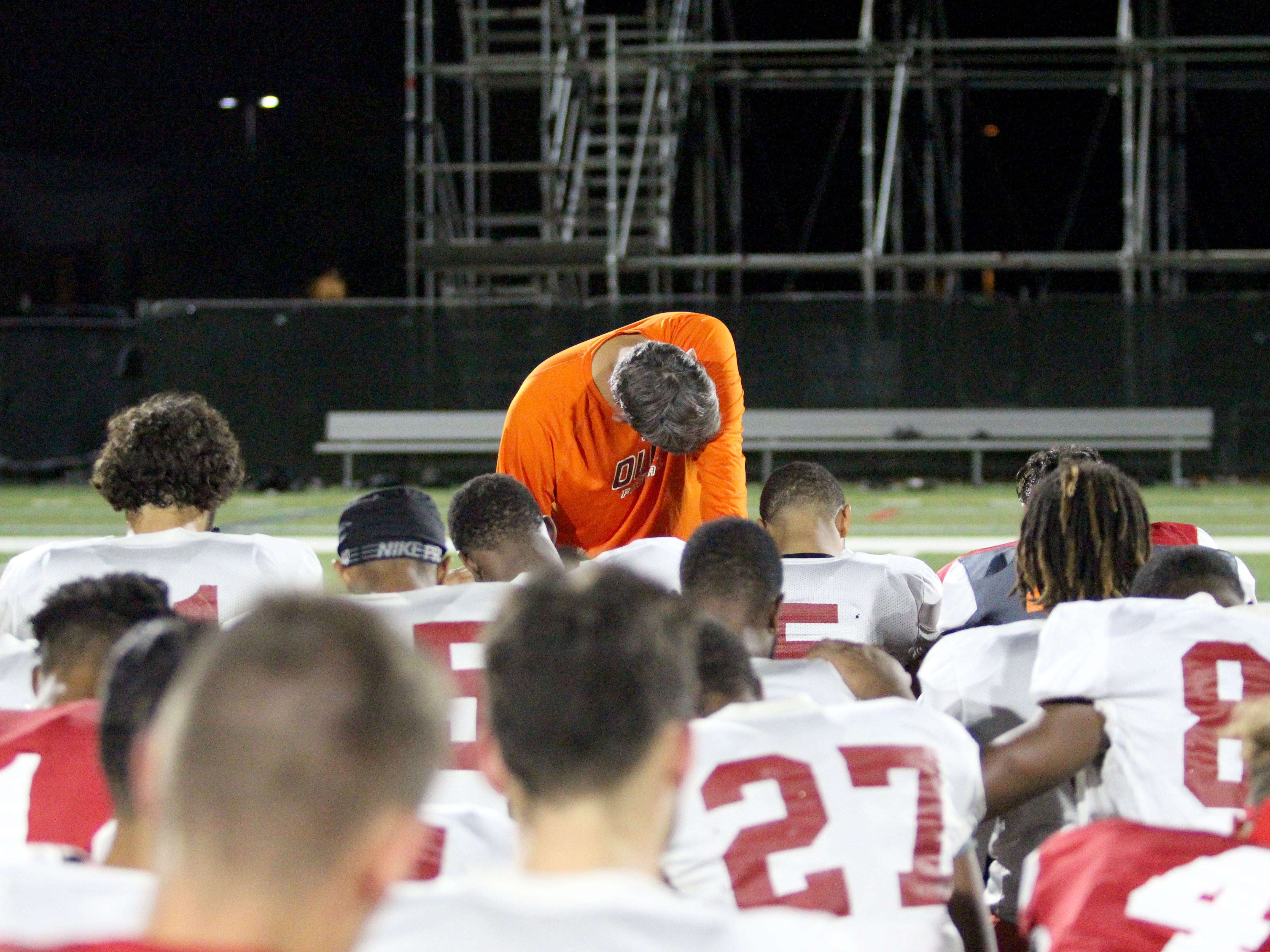 OUAZ coach Mike Nesbitt and his team pray after practice on Tuesday night in Surprise on Sept. 11, 2018.