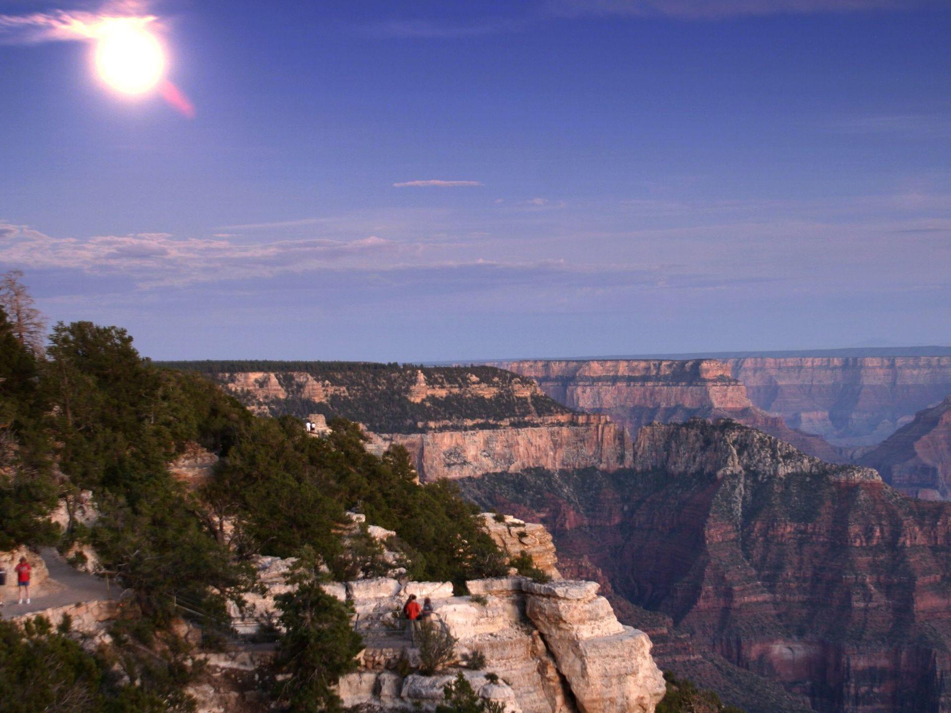 Una luna casi llena ilumina el borde norte del Gran Cañón mientras los últimos excursionistas y visitantes de día salen del cañón y se dirigen hacia la cabaña, el domingo 10 de agosto de 2003.