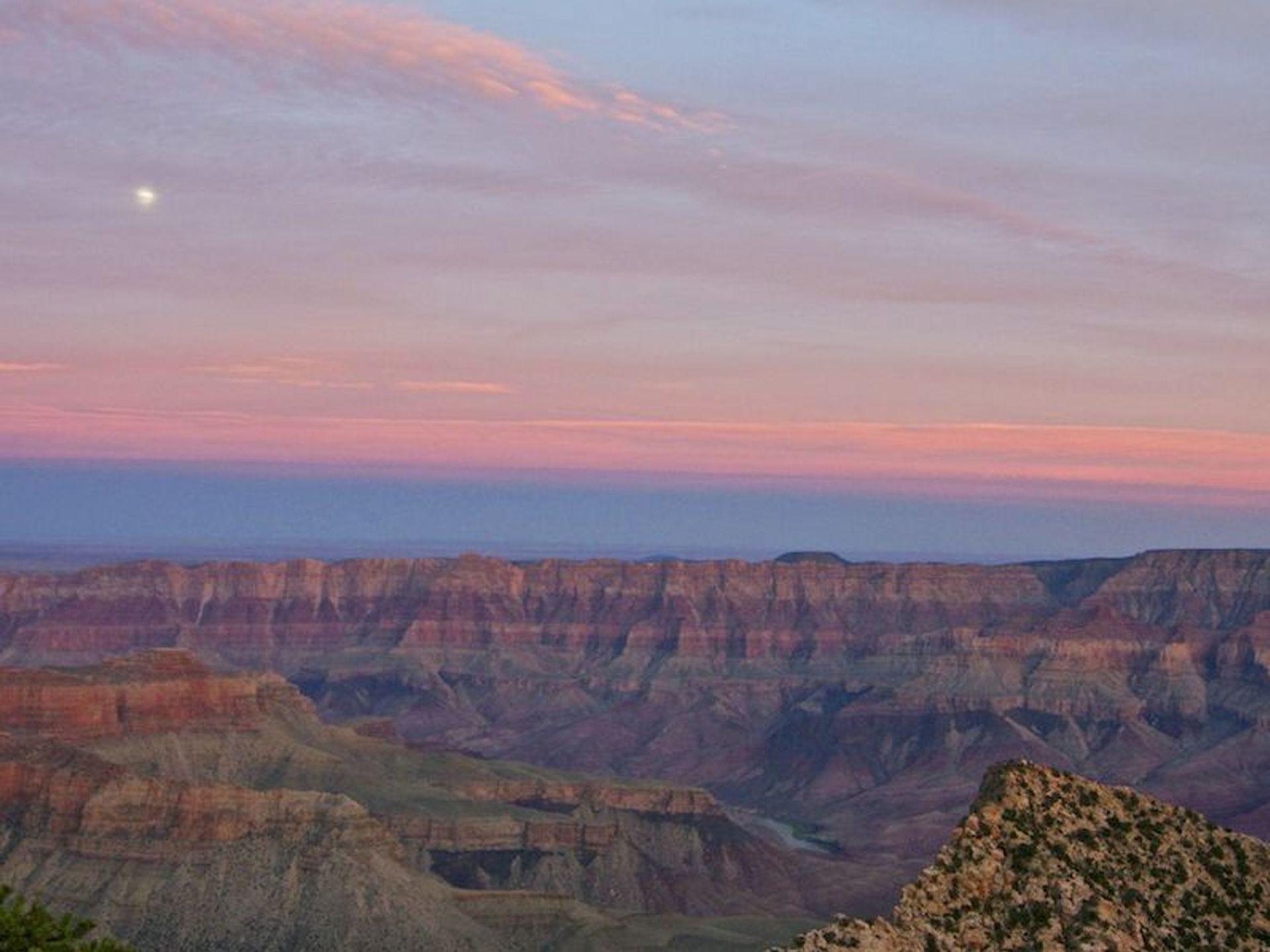 La puesta de sol en el lado oeste de Grand Canyon North Rim. La luna se elevaba en el cielo de color rosa.