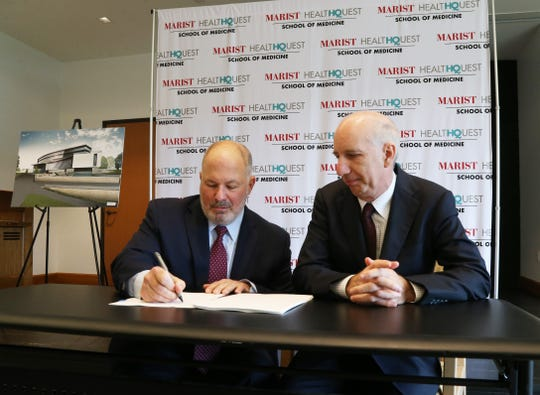 From left, Marist College president David Yellen and HealthQuest CEO Robert Friedberg sign the agreement for the Marist HealthQuest Medical School on Sept 12, 2018.