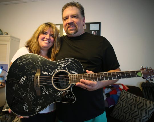 Amanda Schott-Just and Edward Just hold a guitar their wedding guests signed at their home in the Village of Wappingers Falls on September 11, 2018. The couple met on Facebook and were married in August 2018.