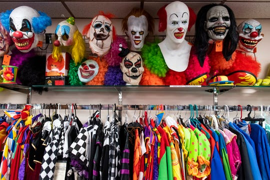 Clown masks hang on display above clown costumes at Make Believin'. Debbi Reck has owned Make Believin' Costumes, in York Township, for 35 years. She said that over the years, costume designs for Halloween have become more creative.