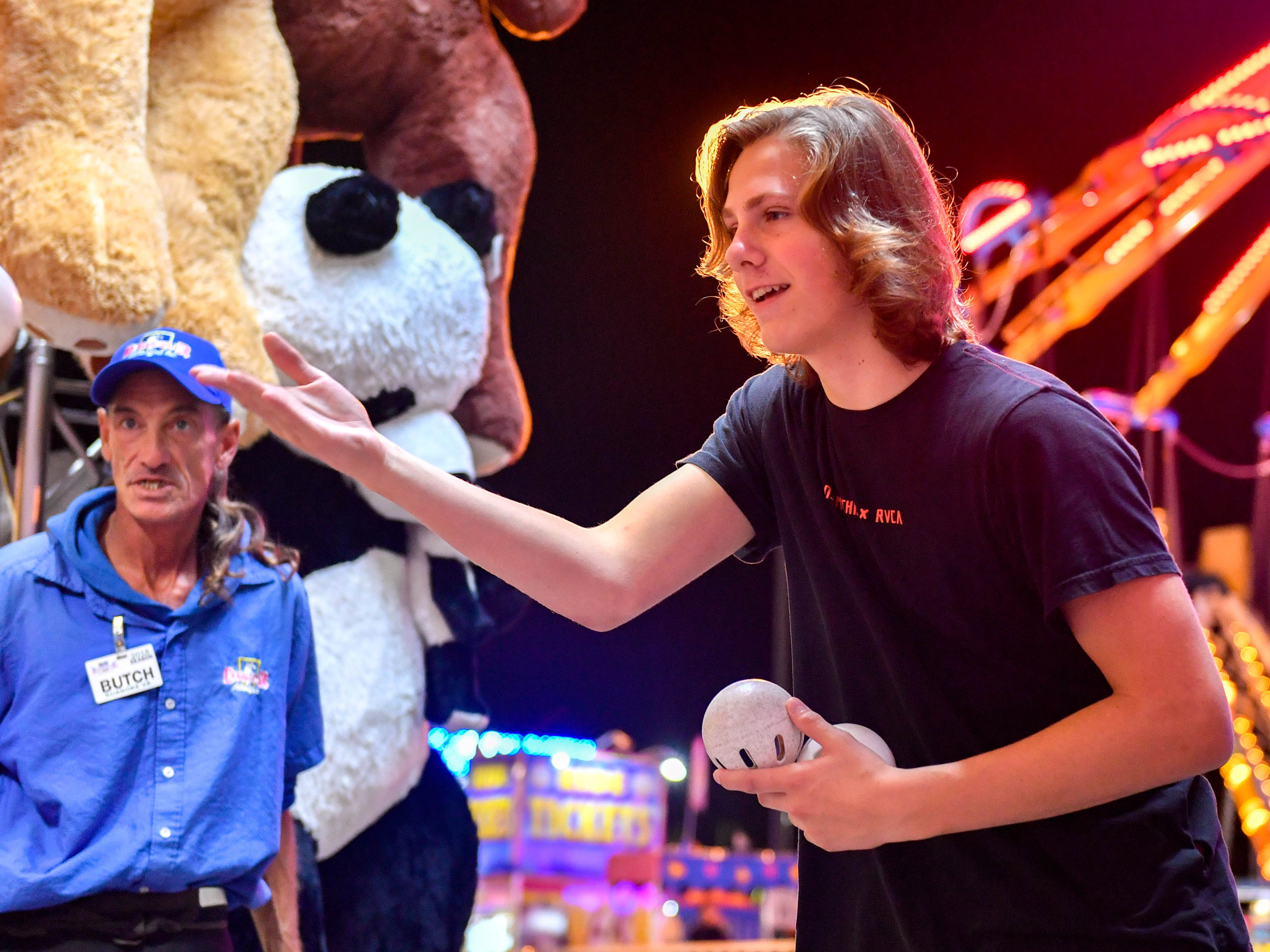 Neon lights are all around as evening fair-goers enjoy games and entertainment at the 2018 York Fair.