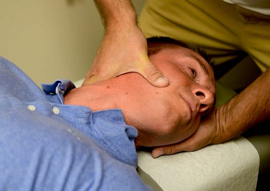 Dr. Kevin Owens, of Chiropractic Athletic Center, works on York Daily Record reporter John Buffone, cracking his neck, on Tuesday, August 28, 2018.