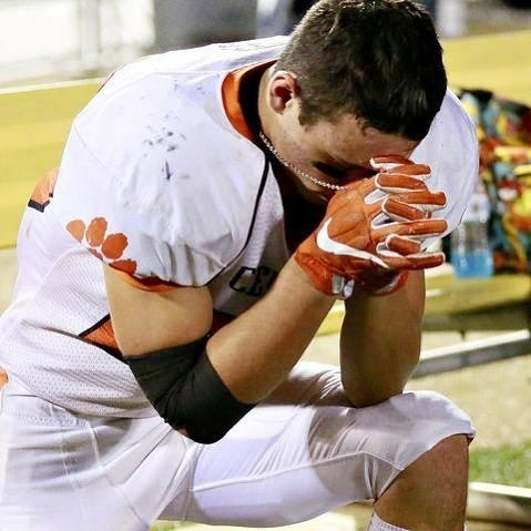 Central York running back Hunter Werner prays for his late stepfather, Ron Kelly, prior to a game this fall.