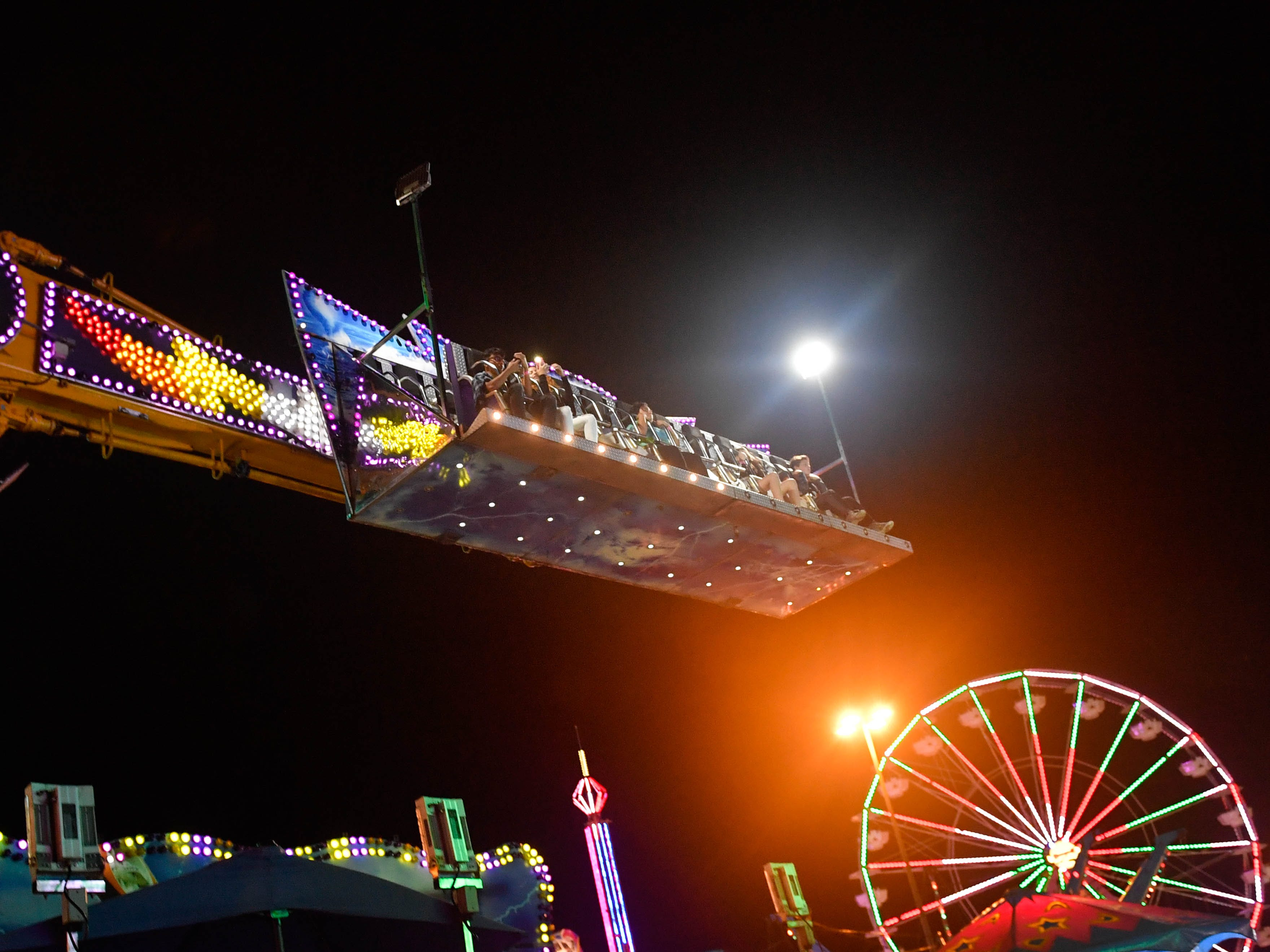 As the Typhoon swings back and forth, riders experience a feeling of weightlessness at the York Fair, Tuesday night, September 11, 2018.