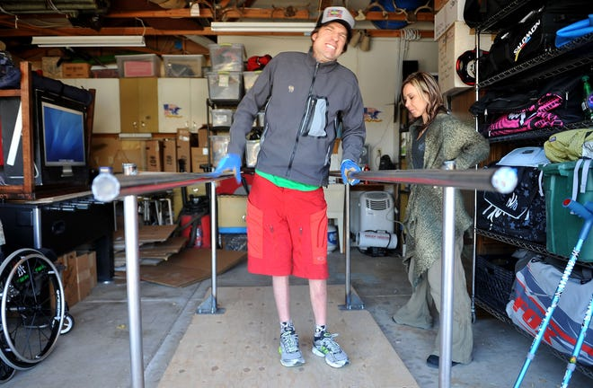 In this 2011 photo, Grant Korgan works on the bars in his garage under the watchful eyes of his wife Shawna.