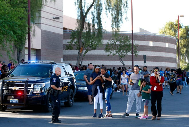 Students and parents wait outside Canyon Springs High School in North Las Vegas after a fatal shooting near a school ball field Tuesday, Sept. 11, 2018. School was out at the time of the shooting but many students were taking part in after-school activities, police said.