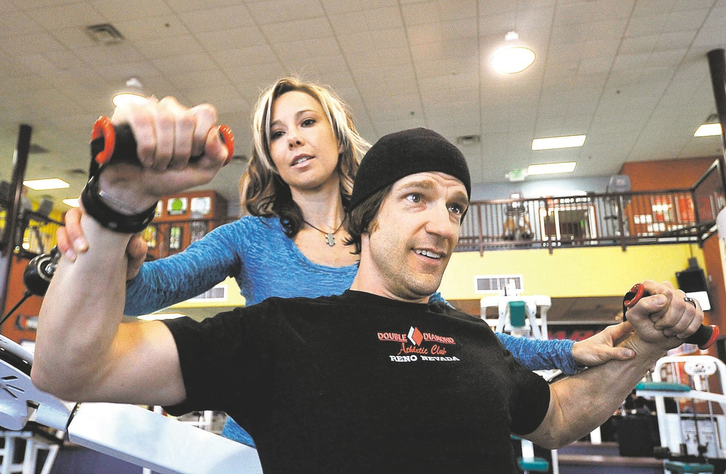 Shawna Korgan helps her husband Grant work on strengthening upper body training at the Double Diamond Athletic Club in 2011.