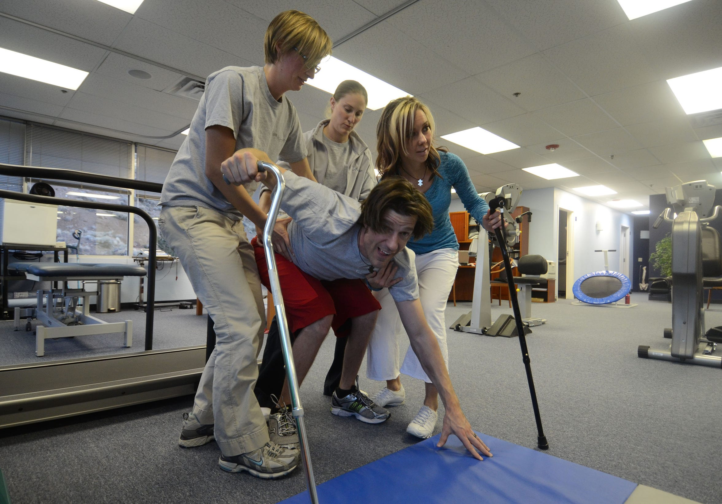 Thais Mollet and Shawna Korgan help Grant up off the matt during a physical therapy session at Spine Nevada.