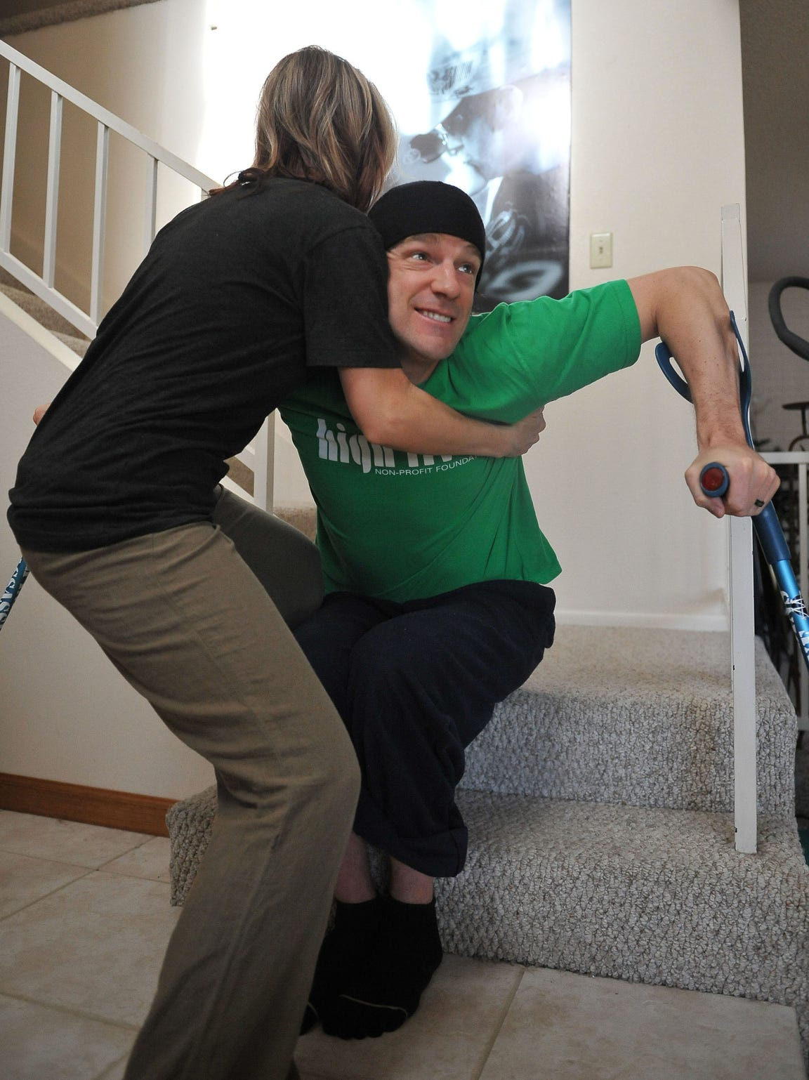 Shawna Korgan helps her husband Grant up from sitting on the steps at their home in 2011.