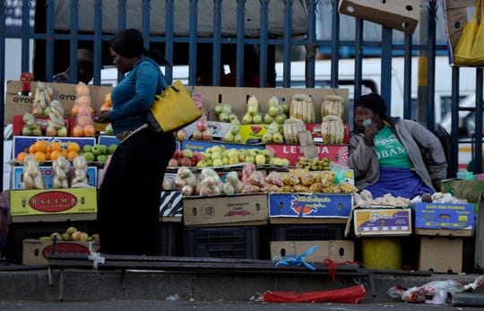 A street vendor selling vegetables, fruits and other items on their stands watches on as a pedestrian walks past her stall in Thokoza south of Johannesburg, South Africa, Tuesday, Sept. 4, 2018. The South African economy has fallen into recession, compounding concerns about its weakening currency, plans for land reform and fallout from state corruption under former president Jacob Zuma. (AP Photo/Themba Hadebe)