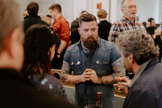 Jason Wood talks with visitors about The Macallan Scotch. Woods is the  bar manager at Misuta Chows and brand ambassador for Edrington (The Macallan, Highland Park).
