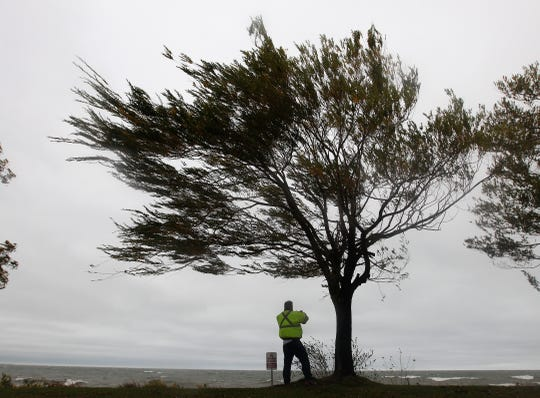 Chris Hunt of Webster fights strong winds as he takes photos of Lake Ontario in Webster as remnants of Hurricane Sandy sweep through.