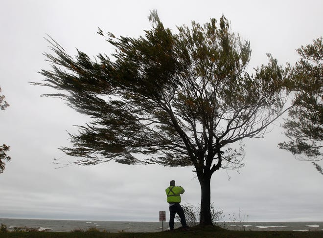 FILE PHOTO: Chris Hunt of Webster fights strong winds as he takes photos of Lake Ontario in Webster as remnants of Hurricane Sandy sweep through.