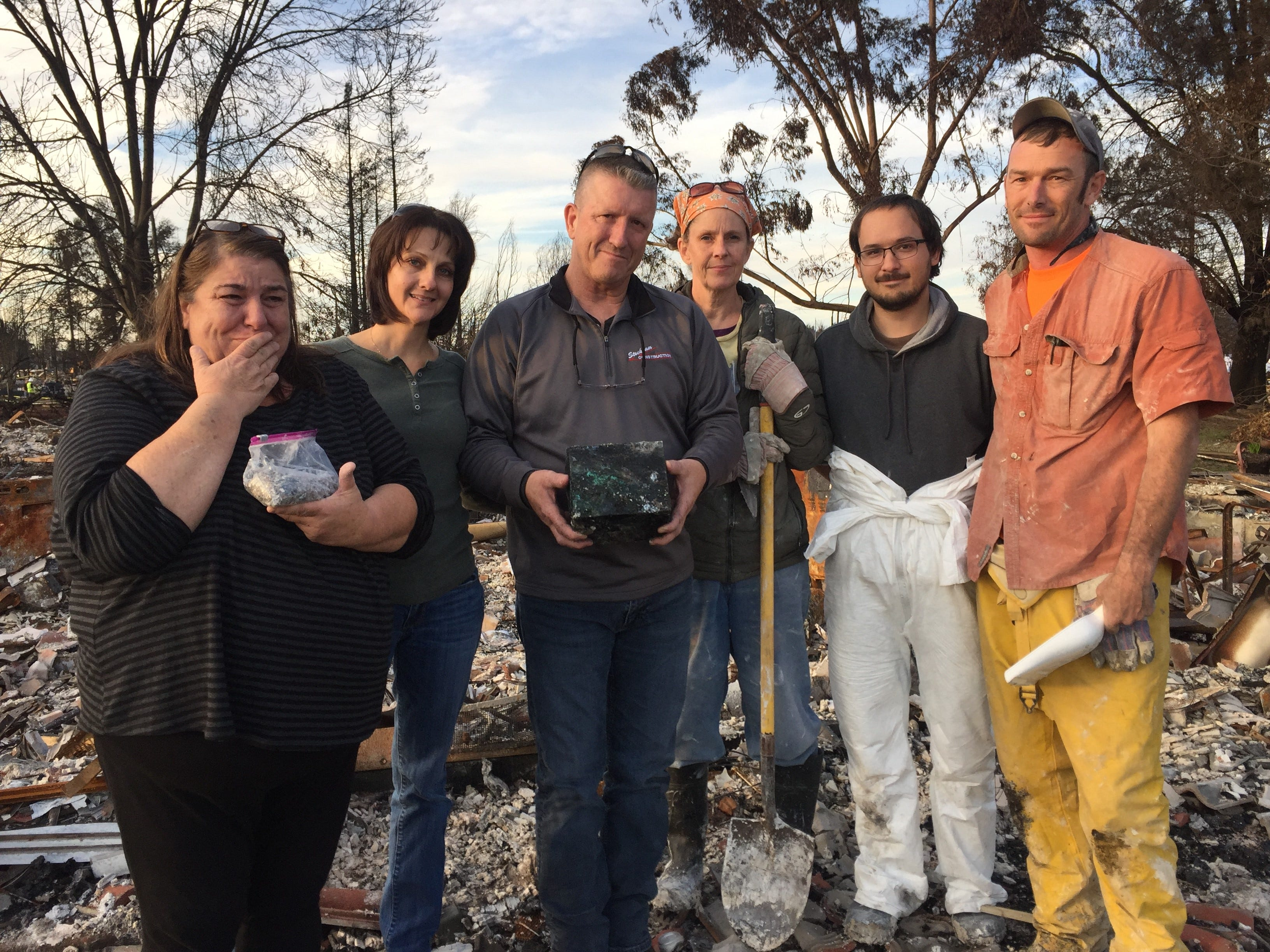 "Nick Rasmussen (third from left) holds his sister's cremains in a box. His sister Debbie Sandoval (left) holds their father's cremains in a bag while Rasmussen's wife Pamela Rasmussen comforts them. The team of archaeologists (three on the right) recovered the cremains after forensic dog ""Piper"" found them in the burned remains of their mother's Santa Rosa home."