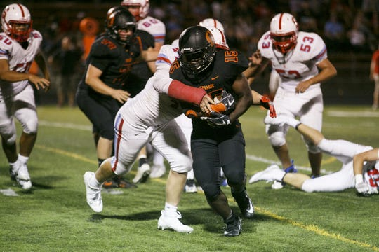 Sprague's Chris Sharp tries to break a tackle from South Salem in the opening game of the season at Sprague High School on Friday, Sept. 1, 2017, in Salem, Ore. Sprague won the game 58-12.