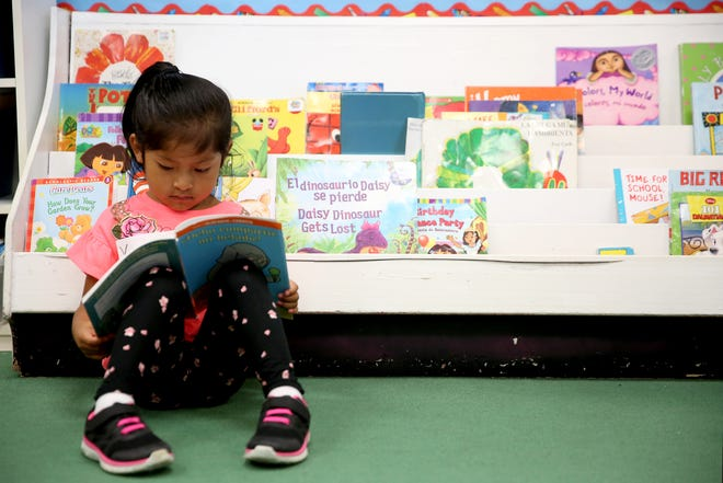 Yoselin Martinez Dolores reads a book on the first day of school of kindergartners at Yoshikai Elementary School in Salem on Wednesday, Sep. 12, 2018.