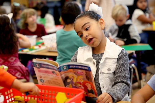 Alexia Trujillo reads a book on the first day of school of kindergartners at Yoshikai Elementary School in Salem on Wednesday, Sep. 12, 2018.